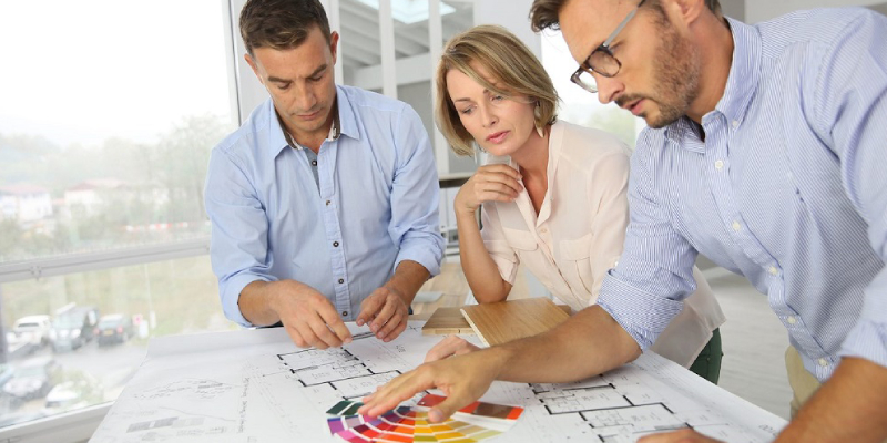 Group of three interoir designers discuusing for a new project